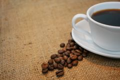 Cup of coffee on burlap background stock image