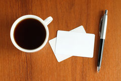 Cup of coffee with business cards and pen Stock Image