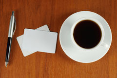 Cup of coffee with business cards and pen Stock Photography