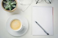 Cup of coffee on business desk next to plant. Elevated view of cup of coffee on business desk next to decorative plant Royalty Free Stock Image