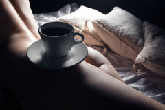 Cup of coffee on buttocks of young nude female; Royalty Free Stock Photo