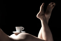Cup of coffee on buttocks of young nude female; Stock Photography