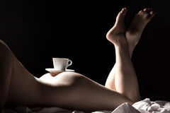Cup of coffee on buttocks of young nude female; Royalty Free Stock Photography