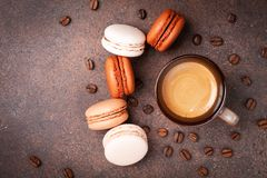 Cup of coffee and cake macaron or macaroon on brown table top view. Delicious breakfast stock photo