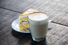 Cup of coffee with cake on old wood table. Cup of latte coffee with yellow cake on old wood table, light nature royalty free stock photography