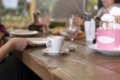 Cup of coffee, cake, people at the wooden dining table, served t. Cup of coffee, cake with pink and white icing, people at the wooden dining table, served table royalty free stock photo