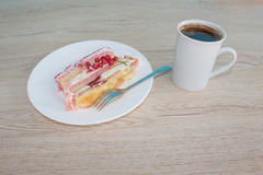 A cup of coffee and cake on wooden background. Cake with fresh red currant on the plate Stock Images