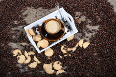 Cup of coffee with cakes. Coffee beans in a coffee cup and some cake, one macaron cake Royalty Free Stock Photos