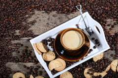 Cup of coffee with cakes. Coffee beans in a coffee cup and some cake, one macaron cake Stock Image