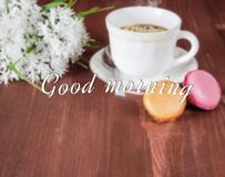 Cup with tea, cakes on the table and flowers on the background Stock Photos