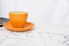 Cup of coffee, calculator and paper with graphs Stock Images