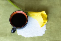 A cup of coffee and a calla. Beautiful yellow calla and cup of coffee on the green napkin royalty free stock image
