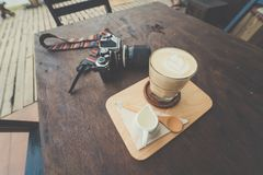 Cup of coffee with  camera. On wooden table Stock Images