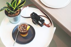 Cup of coffee and camera on the table in cafe. Espresso with lemon honey juice stock images