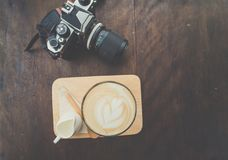 Cup of coffee with  camera. On wooden table Stock Image