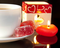 Cup of coffee and candle in the form of heart Stock Images