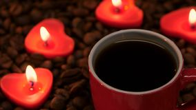 Cup coffee with candles in the shape of heart. Closeup. Red cup of black coffee with lit candles in the shape of heart, coffee beans laid out on the table and stock footage