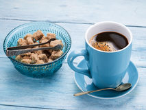 Cup of coffee and cane sugar cubes. Royalty Free Stock Photos