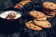 Cup of coffee, cappuccino with chocolate cookies and biscuits on black table background. Afternoon break time. Breakfast. Stock Photos