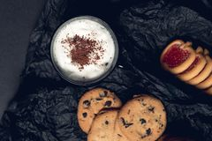 Cup of coffee, cappuccino with chocolate cookies and biscuits on black table background. Afternoon break time. Breakfast. Top view Stock Photos