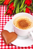Cup of coffee or cappuccino with chocolate heart. Valentines day - cup of coffee or cappuccino with chocolates heart and red tulips on a background Stock Photos