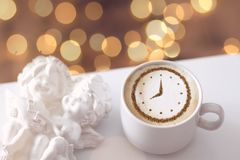 Cappuccino with a clock. A cup of coffee cappuccino with a clock pattern from cinnamon on milk foam royalty free stock photos