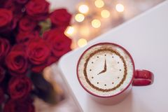 Cappuccino with a clock. A cup of coffee cappuccino with a clock pattern from cinnamon on milk foam stock photography