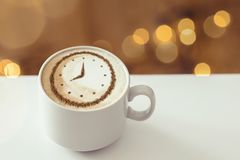 Cappuccino with a clock. A cup of coffee cappuccino with a clock pattern from cinnamon on milk foam stock image