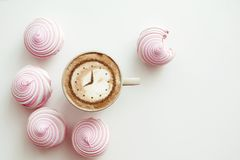 Cappuccino with a clock. A cup of coffee cappuccino with a clock pattern from cinnamon on milk foam stock photos