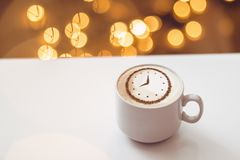 Cappuccino with a clock. A cup of coffee cappuccino with a clock pattern from cinnamon on milk foam royalty free stock images