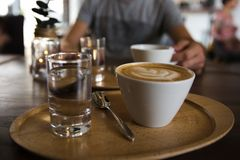 Cup of coffee cappuccino and a glass of water on a wooden tray. A man holding serving cup of coffee on the background royalty free stock images