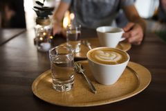 Cup of coffee cappuccino and a glass of water on a wooden tray. A man holding serving cup of coffee on the background royalty free stock photography