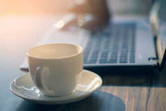 Cup coffee of cappuccino with laptop on the table, coffee shop b Royalty Free Stock Photo