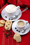 Cup of coffee and cappuccino. Milk and coffee with espresso on background of red cloth and pastries coffee grains Royalty Free Stock Photography