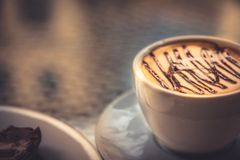 Cup of coffee cappuccino with syrup on glass table in cafe. Classic cup of coffee cappuccino with syrup on glass table in cafe Royalty Free Stock Photo