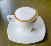 A cup of coffee. A cup of cappuccino  in a white cup on wooden background Stock Photos