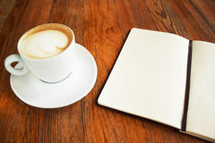 Cup of coffee capuccino with note black book on the wood table like a hipster style Royalty Free Stock Photography