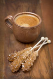 Cup of coffee and caramel sugar on sticks, selective focus Royalty Free Stock Photography