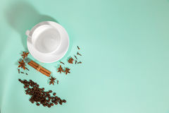 Cup of coffee, Cardamom, grains coffee and cinnamon on a turquoise background Royalty Free Stock Images