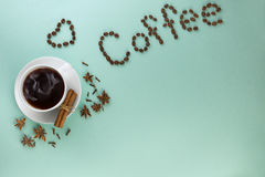 Cup of coffee, Cardamom, grains coffee and cinnamon on a turquoise background Stock Images