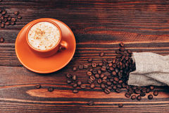 Cup of coffee. Ceramic orange cup of coffee with foam and coffee beans, standing on wooden table Royalty Free Stock Photos