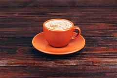 Cup of coffee. Ceramic orange cup of coffee with foam, standing on wooden table on wooden background Royalty Free Stock Photography