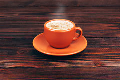 Cup of coffee. Ceramic orange cup of coffee with foam, standing on wooden table on wooden background Stock Image