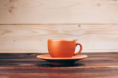 Cup of coffee. Ceramic orange cup of coffee with foam, standing on wooden table on wooden background Stock Photo