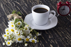 Cup of coffee,chamomile and alarm clock. Royalty Free Stock Photo