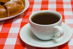 Cup of coffee on checkered red tablecloth with cake on the backg. Round. Close up photo Stock Photos