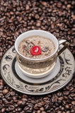 Cup of coffee with cherry  and coffee beans Royalty Free Stock Photography