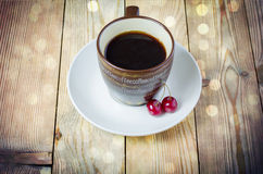 Cup of coffee, cherry. Fofe cup cherries and bokeh Royalty Free Stock Images