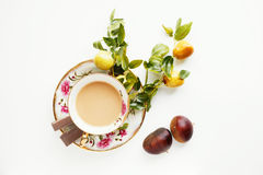 A cup of coffee with chocolate. Beautiful vintage cup full of coffee with little apples, chocolate and chestnuts Stock Image
