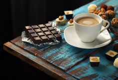 Cup of coffee with chocolate bar and variety of candy Royalty Free Stock Photo